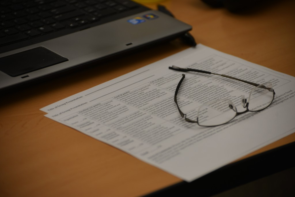 A pair of glasses on top of presentation rubrics